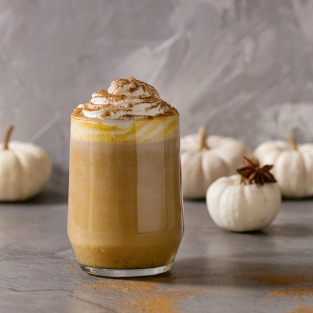 Glass of spicy pumpkin latte with whipped cream and cinnamon standing on gray kitchen table with coffeepot and decorative white pumpkins. Coffee beans and spices above. Square image