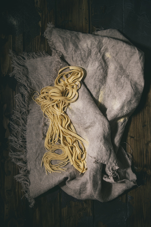 Variety of italian homemade raw uncooked pasta spaghetti and tagliatelle with semolina flour on linen cloth over dark plank texture wooden table. Flat lay, space