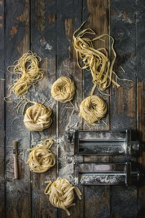 Variety of italian homemade raw uncooked pasta spaghetti and tagliatelle with pasta maker rolled machine and semolina flour over dark plank texture wooden table. Flat lay, space Stock Photo