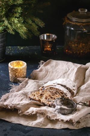Geschnittener Weihnachtskuchen, traditionelles deutsches festliches Backen. Vollkornstollen mit Rosinen und Zuckerpulver auf Leinenserviette auf dunkelblauem Tisch mit Tannenbaum und Kerzen im Hintergrund. Rustikaler Stil