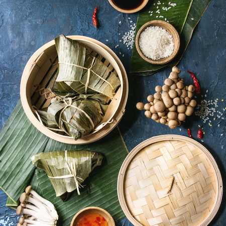 Asian rice piramidal steamed dumplings from rice tapioca flour with meat filling in banana leaves served in bamboo steamer. Ingredients, sauces above. Blue texture background. Top view. Square image