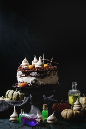 Halloween sweet table with cemetery chocolate cake, marzipan and decorative pumpkins, meringue ghosts, poisons bottles over black wooden table. Stock Photo