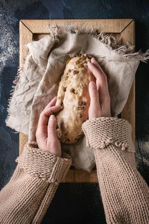 Weihnachtskuchen. Weibliche Hände machen traditionelles deutsches festliches Backen. Vollkornteigstollenzubereitung auf Leinenserviette über dunkelblauem Texturhintergrund. Draufsicht, Raum
