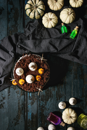Halloween sweet table with cemetery chocolate cake, marzipan and decorative pumpkins, meringue ghosts, poisons bottles over black wooden background. Flat lay, space Stockfoto