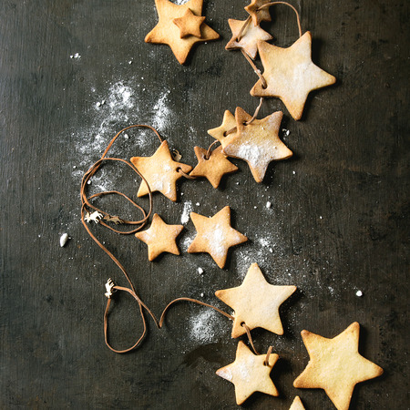 Garland of homemade shortbread star shape sugar cookies different size on thread with sugar powder over dark texture surface. Christmas treat background. Top view with space. Square image