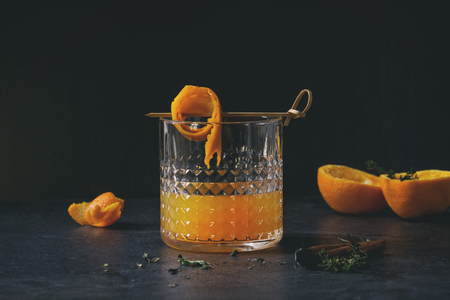 Glass of whiskey orange juice alcohol cocktail with swirled orange peel on skewer, thyme and cinnamon sticks standing on black marble table.