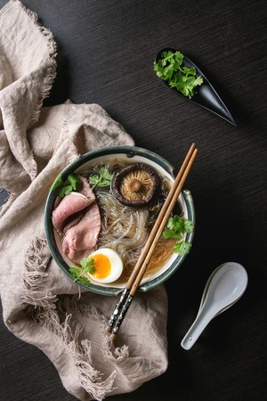 Traditional Japanese Noodle Soup with shiitake mushroom, egg, sliced beef and greens served in ceramic bowl with wooden chopsticks and white spoon on cloth over dark background. Flat lay, space.