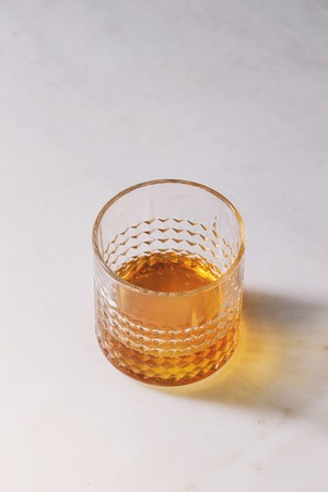 Glass of whiskey standing on white marble background.