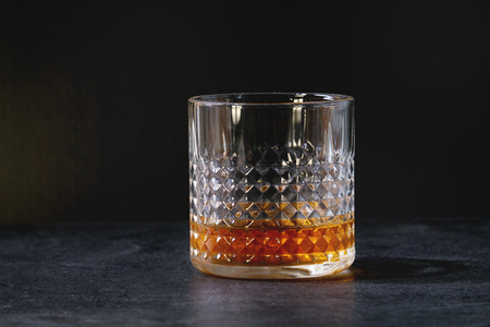 Glass of whiskey standing on black marble table.