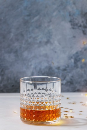 Glass of whiskey standing on white marble table with grey wall at background and golden holiday Christmas stars confetti.