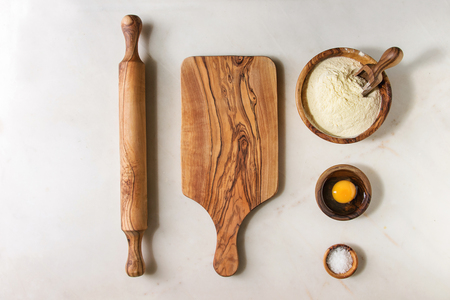 Ingredients for homemade italian pasta ravioli cooking semolina flour, egg yolk, sea salt with olive wood utensils bowls, scoop and rolling pin over white marble background. Flat lay, space