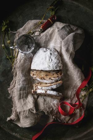Geschnittener Weihnachtskuchen, traditionelles deutsches festliches Backen. Vollkornstollen mit Rosinen und Zuckerpulver auf Leinenserviette mit Sieb, rotem Band, Mistel über altem dunklem Metallhintergrund. Draufsicht