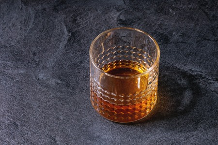 Glass of whiskey standing on black marble table. Alcohol drink.