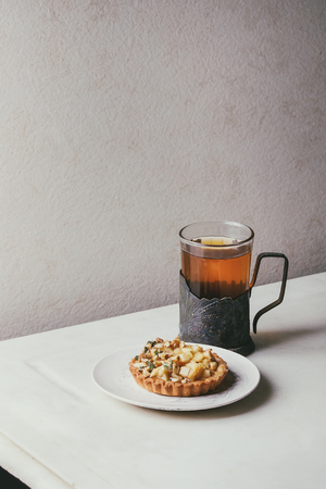 Homemade sweet apple shortbread tartlet in white plate, glass of hot tea in vintage cup holder on white marble table. Autumn baking. Minimalist style.
