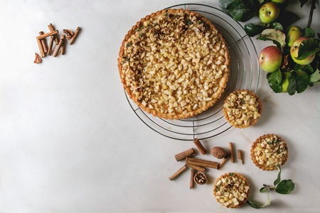 Homemade sweet apple shortbread tart on cooling rack and tartlets with cinnamon sticks, walnuts, apples branches above on white marble background. Autumn baking. Flat lay, space
