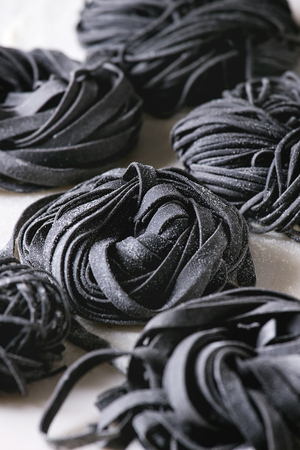 Variety of italian homemade raw uncooked cuttlefish ink black pasta spaghetti and tagliatelle with semolina flour on white marble table. Close up. Zdjęcie Seryjne
