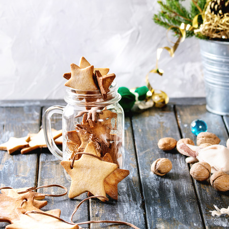 Homemade shortbread star shape sugar cookies different size in glass jar and as garland on old wooden table decorated by Christmas tree and gifts. Christmas mood theme. Square image