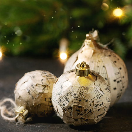 Set of craft paper Christmas balls with vintage music notes with fir tree and lighted garland over dark texture background. Christmas holiday mood card. Close up. Square images