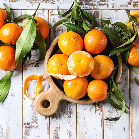 Ripe organic clementines or tangerines with leaves on wood serving board over white wooden plank table as background. Top view, space. Healthy eating. Square images Stock Photo