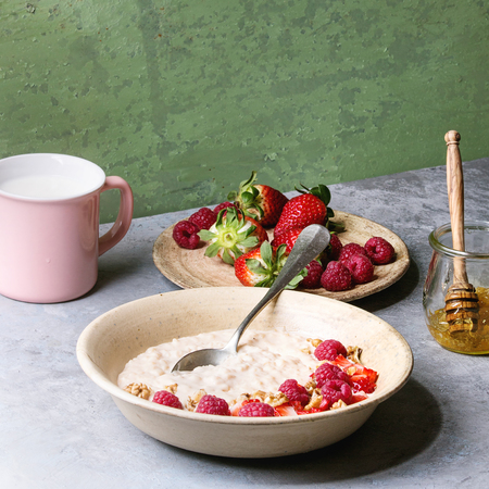 Sweet rice porridge pudding in ceramic plate with berries strawberry and raspberry, walnuts, honey and mug of milk on grey kitchen table with green wall as background. Square image