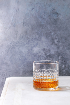 Glass of whiskey standing on white marble table with grey wall at background. Alcohol drink.