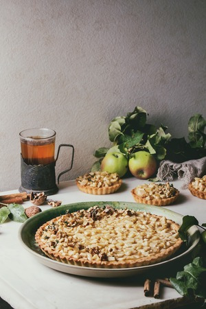 Homemade sweet apple shortbread tart in green ceramic plate, mini tartlets and hot tea in vintage cup holder with cinnamon sticks, walnuts, apples branches above on white marble table. Autumn baking.