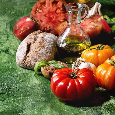 Variety of red and yellow organic tomatoes with olive oil, garlic, salt and bread for salad or bruschetta over green texture background. Close up, copy space. Square image
