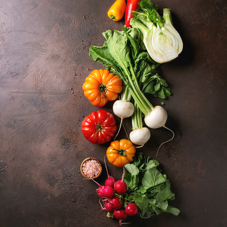 Variety of wet raw fresh organic colorful vegetables tomatoes, radish with leaves, fennel, paprika with bowl of pink salt for salad over dark brown texture background. Top view, space. Square image