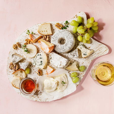 Cheese plate assortment of french cheese served with honey, walnuts, bread and grapes on white wooden serving board, glass of white wine over pink pastel background. Top view, space. Square image Stock Photo