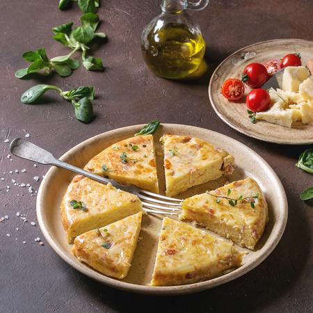 Geschnittene spanische Kartoffelomelett-Tortilla mit Speck serviert in Keramikplatte mit Zutaten oben über dunkelbraunem Texturhintergrund. Quadratisches Bild