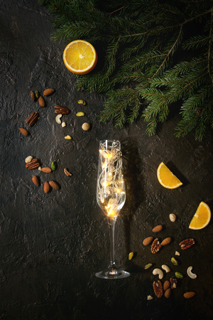 Christmas lights garland in champagne glass with nuts, orange, fir tree branches over dark texture background. Christmas holiday mood card. Top view with space