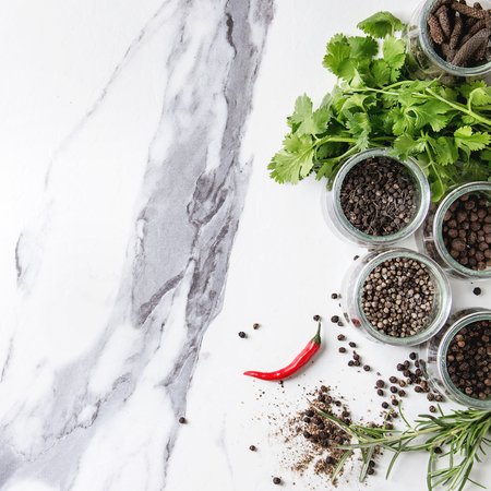 Variety of different black peppers allspice, pimento, long pepper, monks pepper, peppercorns in glass jars, chili pepper and fresh herbs in plate over white marble background. Top view, space. Square image Standard-Bild - 110182282