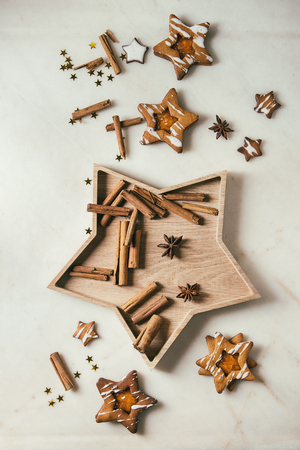 Homemade Christmas star shape sugar caramel cookies with frosting and orange citrus jam, cinnamon sticks and anise over white marble background. Flat lay, space. Sweet xmas or new year gift. Banco de Imagens