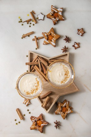 Eggnog Christmas milk cocktail, served in two vintage crystal glasses on wooden tray with shortbread star shape sugar cookies, cinnamon sticks over white marble background. Flat lay, space