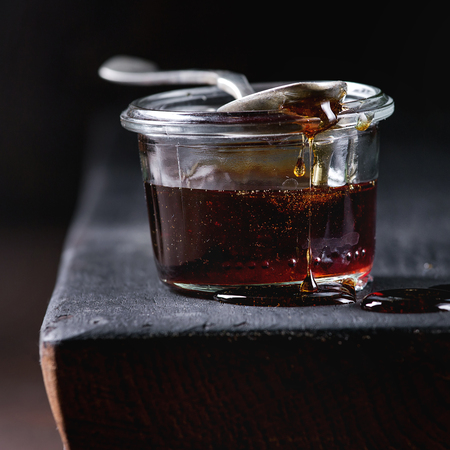 Homemade liquid transparent brown sugar caramel in glass jar standing on black wooden board with spoon. Close up. Square image