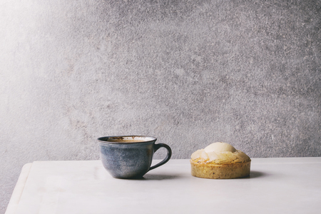 Sweet pear tartlet with cup of coffee espresso standing on white marble table with grey wall at background. Minimalist style. Copy space