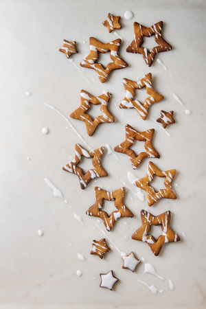 Homemade Christmas star shape sugar caramel cookies with frosting over white marble background. Flat lay, copy space. Sweet xmas or new year gift.
