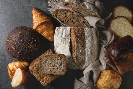 Variety of fresh baked rye, spelled, wheat craft artisan bread, whole and sliced, on cloth over black texture background. Flat lay, space Stock fotó - 110183543