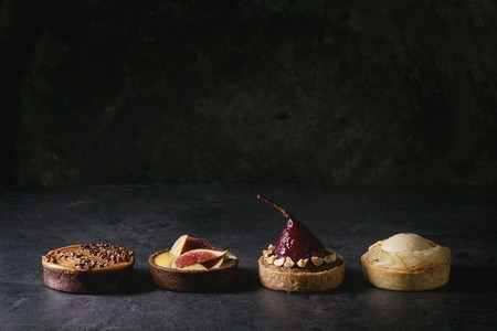 Variety of sweet tartlets with chocolate, caramel, pears, figs in row on black texture table. Stockfoto