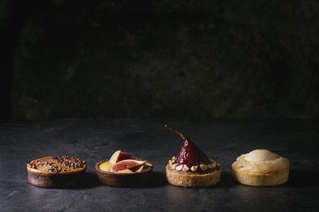 Verscheidenheid aan zoete taartjes met chocolade, karamel, peren, vijgen in rij op zwarte textuurtafel. Stockfoto