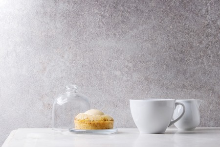 Sweet pear tartlet with cup of coffee espresso and jug of cream standing on white marble table with grey wall at background. Minimalist style. Copy space