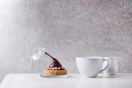 Sweet red wine pear tartlet with cup of coffee espresso and jug of cream standing on white marble table with grey wall at background. Minimalist style. Copy space Stock Photo