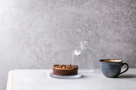 Sweet chocolate tartlet with cup of coffee espresso standing on white marble table with grey wall at background. Minimalist style. Copy space Stock Photo