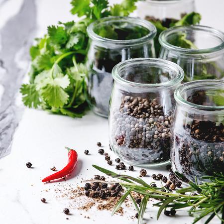Variété de différents piments noirs, piment, poivre long, poivre des moines, grains de poivre et poudre moulue dans des bocaux en verre avec du piment et des herbes fraîches sur une table de cuisine en marbre blanc. Image carrée