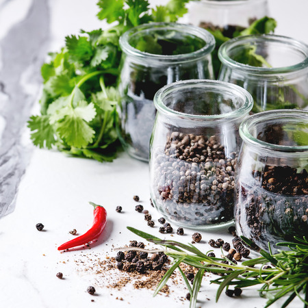 Variety of different black peppers allspice, pimento, long pepper, monks pepper, peppercorns and ground powder in glass jars with chili pepper and fresh herbs on white marble kitchen table. Square image Standard-Bild - 110775377