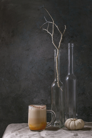 Glass of pumpkin layered spice latte with pumpkin puree, milk foam and cinnamon standing with bottles, branch, decorative white pumpkins on crumpled table cloth. Interior style. Dark mood