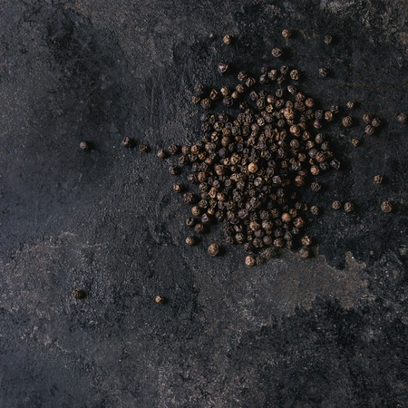 Heap of black pepper peppercorns over old black iron texture background. Top view, copy space. Square image