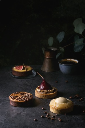 Variety of sweet tartlets with chocolate, caramel, pears, figs with cup of coffee and coffee beans around on black texture table.
