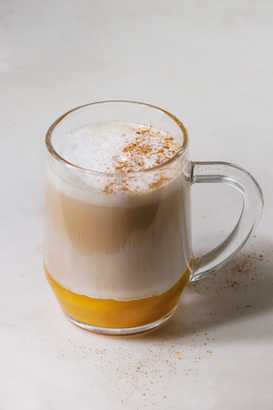 Glass of pumpkin layered spice latte with pumpkin puree, milk foam and cinnamon standing on white marble table. Close up Фото со стока