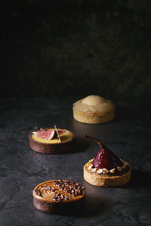 Variety of sweet tartlets with chocolate, caramel, pears, figs on black texture table. 写真素材